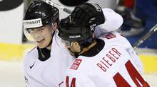 Matthias Bieber, right, from Switzerland congratulates to his teammate Raphael Diaz, left, after scoring against Canada. (Petr David Josek/Associated Press)