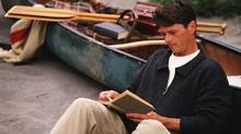 A man on a beach with a canoe and a book.