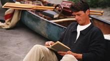 A man on a beach with a canoe and a book.