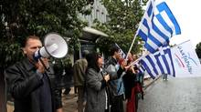 Supporters from the Independent Greeks party wave Greek flags during a protest outside a debt collection agency in Athens last month. (Petros Giannakouris/Associated Press)