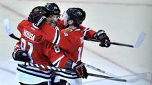 Chicago Blackhawks' Jonathan Toews with teammates Patrick Sharp and Marian Hossa (Paul Beaty/The Associated Press)