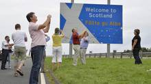 Swiss tourists take photographs next to a road that marks the England - Scotland border, at a lay-by on the A1 road near Berwick August 20, 2013. (TOBY MELVILLE/REUTERS)