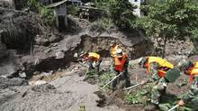 Rescue workers search for survivors after a landslide in Fugong county, Yunnan province, July 9, 2014. According to Xinhua News Agency, 17 people went missing and one was injured after the landslide near Nujiang River on Wednesday. (CHINA DAILY/REUTERS)