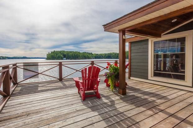 Muskoka chairs sit on the deck of the boathouse, which features its own living quarters.