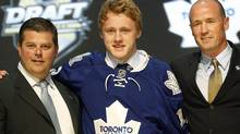 Morgan Rielly, centre, a defenceman, stands with officials from the Toronto Maple Leafs after being chosen fifth overall in the first round of the NHL hockey draft on Friday, June 22, 2012, in Pittsburgh. (Keith Srakocic/AP)