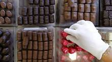 A shop assistant adjusts pralines in a counter at a Leonidas chocolate boutique in Brussels September 28, 2011. (YVES HERMAN/REUTERS)