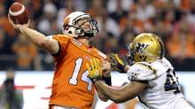 BC Lions quarterback Tavis Lulay throws a pass as he is pressured by Winnipeg Blue Bombers' Rodney Fritz (TODD KOROL/REUTERS)