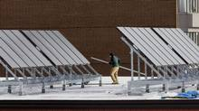 A worker installs solar panels on the roof of the police station in Halifax on Tuesday, Jan. 18, 2011. (Andrew Vaughan/The Canadian Press)
