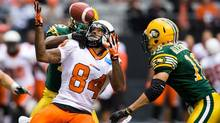 B.C. Lions' Emmanuel Arceneaux, left, bobbles a pass as Edmonton Eskimos' Chris Rwabukamba, back, defends before Donovan Alexander, right, made the interception and ran the ball to the two-yard-line during the first half of a preseason CFL game in Vancouver, B.C., on Friday June 21, 2013. (DARRYL DYCK/THE CANADIAN PRESS)