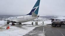 A WestJet Boeing 737-700 aircraft ended up in the mud off an apron next to the Kelowna International Airport terminal Monday morning, Jan. 7, 2013. Two large tandem tow trucks attached cables to its rear wheels and slowly pulled it back onto the pavement. The 138 passengers and six crew disembarked with passengers booked on other flights or given hotel vouchers. (J.P. SQUIRE/THE CANADIAN PRESS)