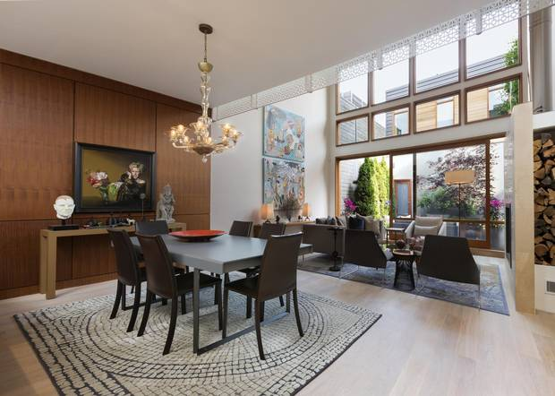 Floor-to-ceiling windows provide views into a pocket garden in the combined living and dining area, which includes a secondary entrance that allows for direct access to the kitchen from the laneway parking.