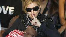 Madonna quietens adopted Malawian child Mercy James during a visit to Gumulira village, about 80 km from the Malawian capital of Lilongwe, during an April 2010 visit to the country. (Reuters)