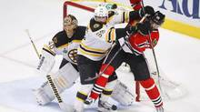Boston Bruins' Johnny Boychuk (55) battles with Chicago Blackhawks' Michal Handzus (26) as Boston Bruins goalie Tuukka Rask tries to see the play during the third period in Game 2 of their NHL Stanley Cup Finals series in Chicago, Illinois, June 15, 2013. (JEFF HAYNES/REUTERS)