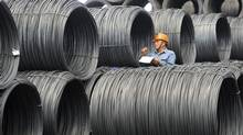 A worker checks stocks of steels at a steel maker in Zhangjiagang in east China's Jiangsu province. (Associated Press)