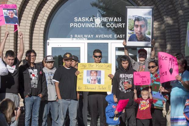 Family, friends and supporters of Colten Boushie hold signs during a rally outside of the Saskatchewan Provincial Court in North Battleford, Sask. on Aug. 18.