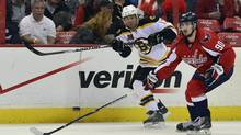Boston Bruins right wing Jarome Iginla passes the puck up the ice past Washington Capitals centre Marcus Johansson during the third period at Verizon Center. (Tommy Gilligan/USA Today Sports)