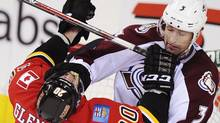Calgary Flames' Curtis Glencross takes a hit from Colorado Avalanche's Ryan O'Byrne during the second period of their NHL hockey game in Calgary, Alberta, March 27, 2013 (Reuters)