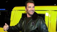 Arnold Schwarzenegger arrives at the premiere of his new film The 6th Day in his yellow Hummer car, in Los Angeles, 13 November 2000. (LUCY NICHOLSON)