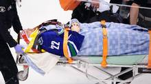 Vancouver Canucks forward Daniel Sedin (22) is taken by stretcher off the ice after a hit by the Calgary Flames during the second period at Rogers Arena, April 13, 2014. (Anne-Marie Sorvin/USA TODAY Sports)
