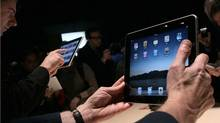 Guests play with the new Apple iPad during a special event in January, in San Francisco. (Justin Sullivan/2010 Getty Images)
