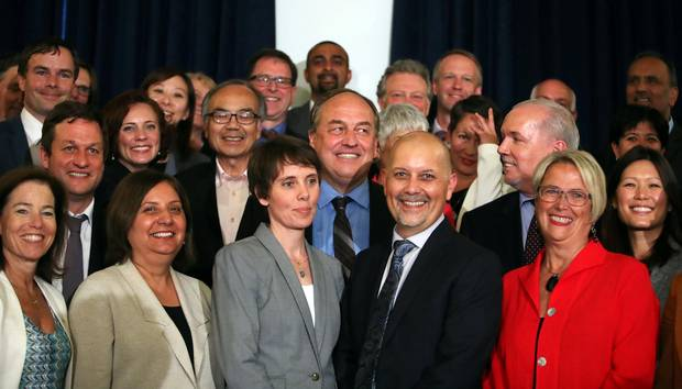 BC Green leader Andrew Weaver and BC New Democrat leader John Horgan look at each other while standing with all Member of the Legislative Assembly-elect from the B.C. Green and New Democrat caucuses.