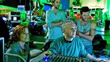 James Cameron (seated) reviews a scene with actors Sigourney Weaver, Joel David Moore and Sam Worthington. (Mark Fellman)