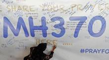 A woman writes a message of support and hope for the passengers of the missing Malaysia Airlines MH370 on a banner at Kuala Lumpur International Airport March 12, 2014. The search for the missing Malaysia Airlines Boeing 777 jetliner expanded on Wednesday to cover an area stretching from China to the Andaman Sea, with authorities no closer to explaining what happened to the plane or the 239 people on board. (DAMIR SAGOLJ/REUTERS)