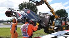 Track workers remove the car of Sauber driver Esteban Gutierrez of Mexico after a crash at the Canadian Grand Prix, Saturday, June 8, 2013 in Montreal. (Tom Boland/THE CANADIAN PRESS)