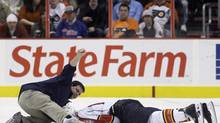 A trainer signals for a doctor while tending to Florida Panthers forward David Booth, who was blindsided by Mike Richards of the Philadelphia Flyers in an Oct. 24 game. (Matt Slocum/AP)