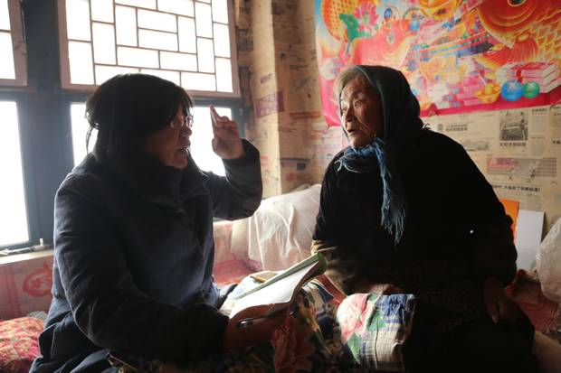 Professor Jia Shuhua of Dalian Medical University speaks with an elderly woman whose husband died by suicide.