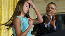 President Barack Obama applauds Victoria Bellucci, a 2014 graduate of Huntingtown High School in Huntingtown, Md., as she introduces him to speak at the White House Healthy Kids & Safe Sports Concussion Summit on Thursday. (Susan Walsh/AP)