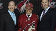 Max Domi, a center, stands with officials from the Phoenix Coyotes sweater after being chosen 12th overall in the first round of the NHL hockey draft (Bill Kostroun/The Associated Press)