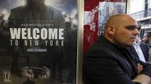 """A man stands next to a poster of the film """"Welcome to New York"""" directed by Abel Ferrara at a movie theatre ahead of a premiere screening during the 67th Cannes Film Festival in Cannes May 17, 2014. (© Eric Gaillard / Reuters)"""
