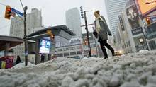 A pedestrian makes her way through the snow and slush in downtown Toronto, Feb, 2, 2011. (Darren Calabrese / CP/Darren Calabrese / CP)