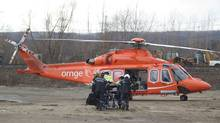 A person injured in the Via Rail passenger train derailment is moved to a Ornge helicopter to be air lifted to hospital in Burlington, Ont. on Sunday, February 26, 2012. (Pawel Dwulit/Pawel Dwulit/CP)