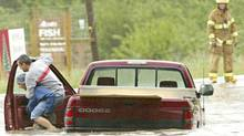 A Calgary driver gives a piggy back ride to his passenger on a flooded Bannister Rd. in Calgary, Alta. on Saturday June 18, 2005. (Jack Cusano/CP)