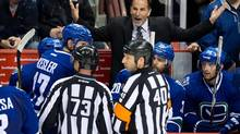 Vancouver Canucks' head coach John Tortorella, top, argues with referee Steve Kozari, 40, and linesman Vaughan Rody, 73, during second period NHL action against the Los Angeles Kings in Vancouver, B.C., on Monday November 25, 2013. (DARRYL DYCK/THE CANADIAN PRESS)