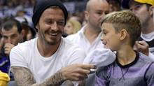 Soccer player David Beckham, left, hits his son Romeo in the face with a towel after he was given a puck that went into the crowd as they watch the Los Angeles Kings play the Phoenix Coyotes in Game 4 of the NHL hockey Stanley Cup Western Conference finals, Sunday, May 20, 2012, in Los Angeles. (Associated Press)