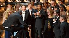 """Director Steve McQueen, left, celebrates with the cast and crew of """"12 Years a Slave"""" as they accept the award for best picture during the Oscars at the Dolby Theatre on Sunday, March 2, 2014, in Los Angeles. (John Shearer/Invision/AP)"""