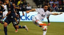 Vancouver Whitecaps midfielder Pedro Morales (77) takes possession of the ball against Los Angeles Galaxy midfielder Stefan Ishizaki (24) during the first half at BC Place, April 19, 2014. (Anne-Marie Sorvin/USA Today Sports)