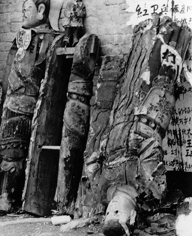 "Wooden religious statues from a Buddhist temple lean against a temple wall in a Beijing suburb in August, 1966, after the Red Guard – setting out to destroy the ""old superstitions of old China"" – knocked the statues off their pedestals."