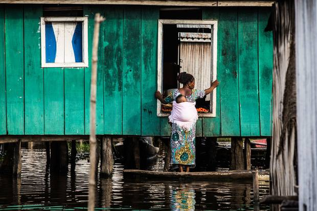 A woman stands on her boat outside of a house in So-Ava. For many in the community, small canoes are their only link to the outside world.