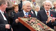 Former B.C premier Gordon Campbell holds up the pipes of Victoria Cross recipient James Richardson at a repatriation ceremony at the B.C. Legislature in Victoria in 2006, as Speaker Bill Barisoff, left and Patrick Reid of the Canadian Club look on. Mr. Richardson was Canada's only piper to be awarded a Victoria Cross. (Adrian Lam/The Canadian Press/Adrian Lam/The Canadian Press)