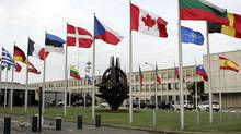 National flags are seen outside NATO headquarters in Brussels. (Virginia Mayo/AP)