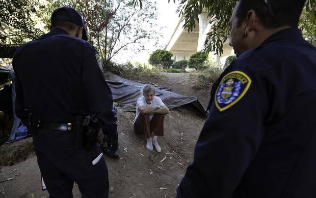 Police encourage homeless man Stephen Schofield to get a hepatitis A vaccination near where Mr. Schofield is living along the San Diego River in San Diego. A recent hepatitis A outbreak reflects how much homelessness has become a crisis in San Diego.