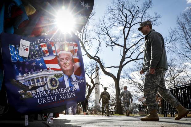 Military personnel walk along the National Mall in Washington on Wednesday - days before Donald Trump's presidential inauguration.