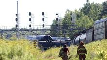 Firefighters walk near a derailed train near Brockville, Ont., on July 10, 2014, after 26 cars jumped the tracks. (LARS HAGBERG/THE CANADIAN PRESS)