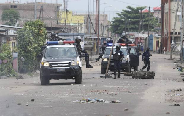 Riot police remove barricade used to block a road during a protests in Kinshasa, Democratic Republic of Congo, Tuesday, Dec. 20, 2016. Human Rights Watch says security forces have killed three people in Congo's capital and arrested scores more amid protests against President Joseph Kabila's hold on power.