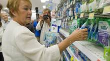 Parti Quebecois leader Pauline Marois looks at razor blades at a pharmacy during an election campaign stop in Repentigny, Que., Saturday, August 11, 2012. (Graham Hughes/THE CANADIAN PRESS)