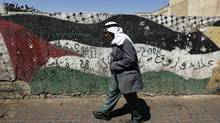 A Palestinian walks past a Palestinian flag painted on a wall in West Bank city of Ramallah Sept.19, 2011. (Ammar Awad/Reuters/Ammar Awad/Reuters)